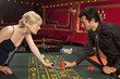 Man and woman placing bets at roulette table