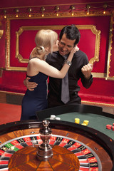 Girlfriend kissing winning boyfriend at roulette table