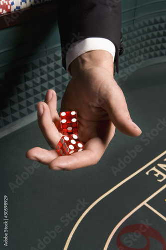 Man?s hand holding dice at craps table