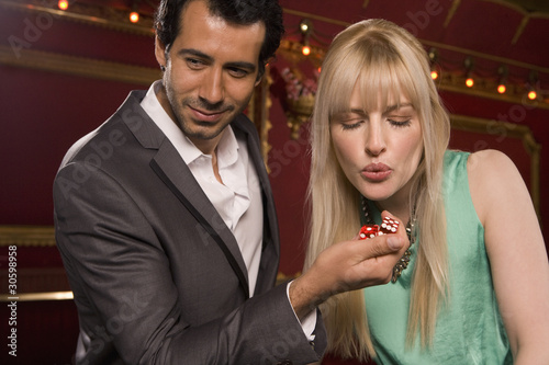 Girlfriend blowing on boyfriend?s dice in casino