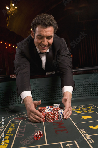 Man gathering winnings at craps table