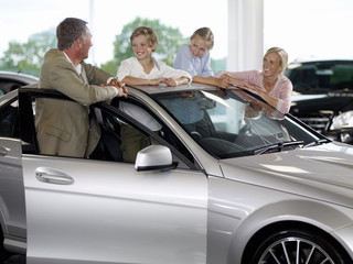 Family looking at new car in showroom