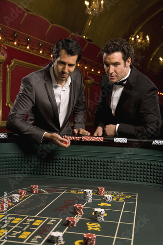 Friends throwing dice at craps table