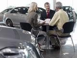 Salesman talking to couple in automobile showroom