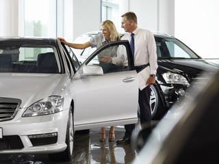 Salesman talking to woman in automobile showroom