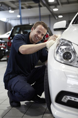 Mechanic waxing new car in showroom