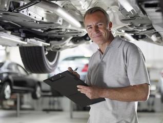 Mechanic working underneath car in auto repair shop