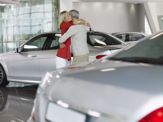 Happy couple hugging in automobile showroom