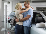 Couple hugging in automobile showroom