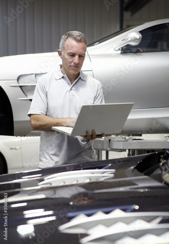 Mechanic using computer auto repair shop