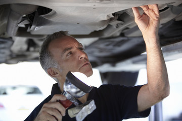 Mechanic working underneath car
