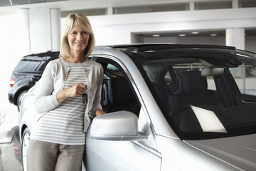 Woman leaning against new car in showroom