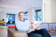 Smiling man reading newspaper on couch