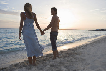 Happy couple holding hands on beach