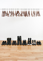 Row of shoes and empty hangers
