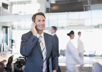Businessman talking on cell phone in busy office