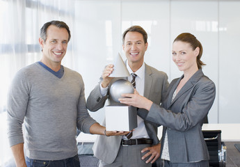"""""""Business people holding cube, sphere and cone"""""""