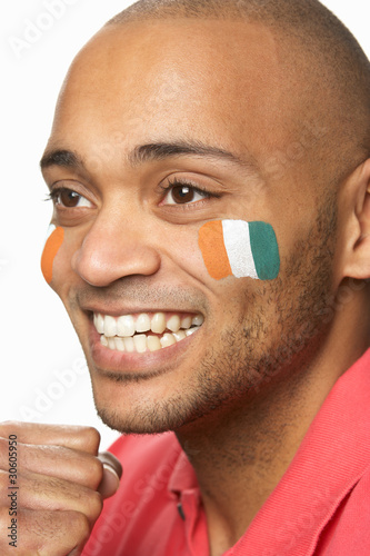 Young Male Sports Fan With Ivory Coast Flag Painted On Face