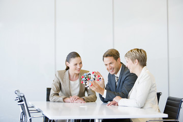 Business people looking at molecule model in conference room