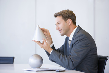 Businessman in conference room looking at cone