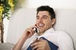 Mann entspannt zuhause am Telefon