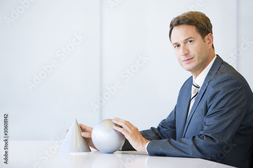 Businessman sitting at table with cone and sphere