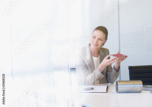 Businesswoman holding circuit board in office