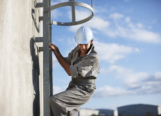 Worker in hard-hat climbing down outdoor ladder