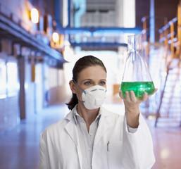 Scientist in protective mask examining liquid in beaker