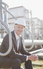 Businessman in hard-hat sitting on industrial steps