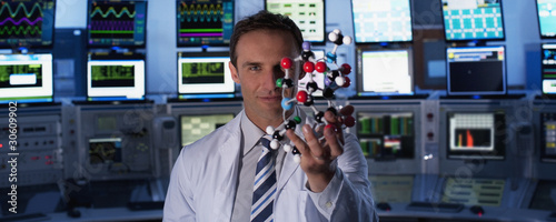 Scientist holding molecule model in control room