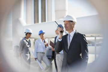 Businessman in hard-hat talking on walkie-talkie outdoors