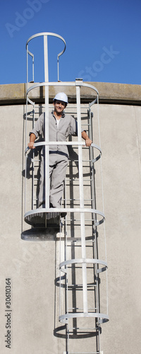 Worker in hard-hat standing on outdoor ladder