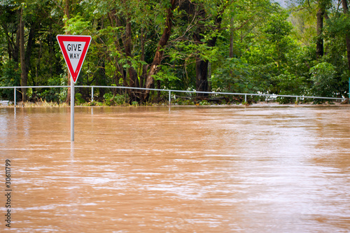 Very flooded road and give way sign, Queensland, Australia