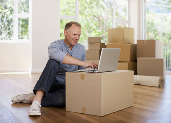 Man using laptop on box in new house