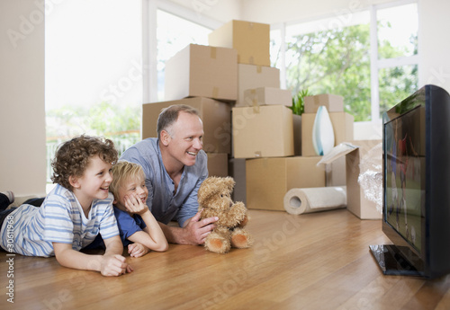 Father and children watching television in new house
