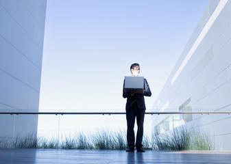 Businessman holding glowing laptop on balcony
