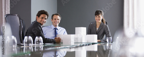 Business people stacking white cubes in conference room