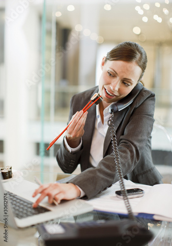 Businesswoman eating sushi and working at desk