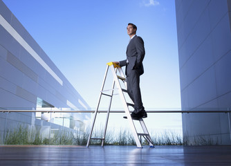 Businessman standing on ladder on balcony