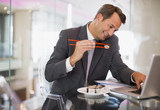 Businessman eating sushi and talking on telephone