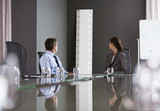 Business people looking at large ruler in conference room