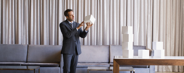 Businessman stacking white cubes in hotel lobby