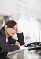 Businesswoman staring at telephone waiting for it to ring