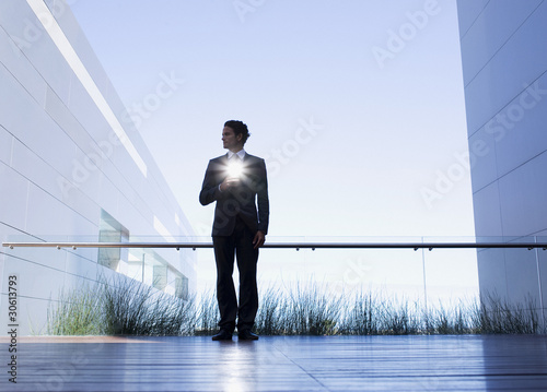 Businessman with glowing light on balcony