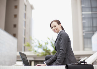 Businesswoman using laptop on lounge chair outdoors