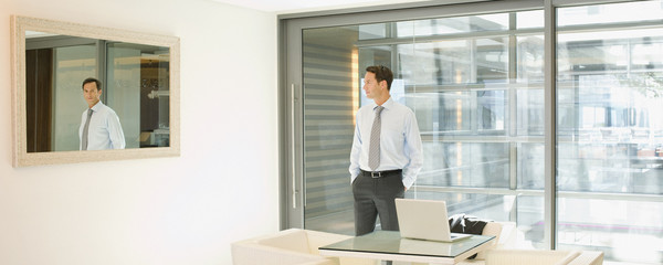 Businessman looking at his reflection in office