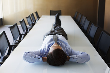 Businessman laying on conference room table