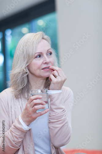 Mature woman taking medicine