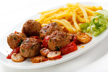 Roasted meatballs, French fries and vegetables
